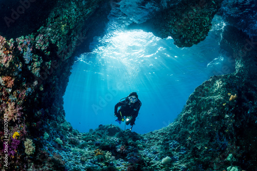 Obraz woman diver underwater at the entrance of a cave with sunrays - fototapety do salonu