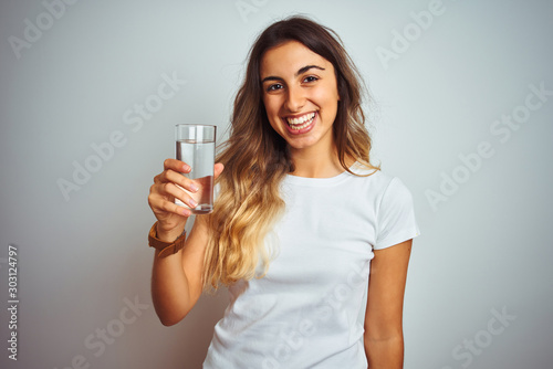 Obraz na płótnie Young beautiful woman drinking a glass of water over white isolated background w