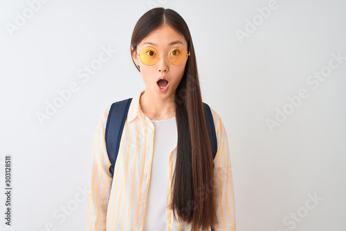 Obraz Young chinese student woman wearing glasses and backpack over isolated white background afraid and shocked with surprise expression, fear and excited face. - fototapety do salonu