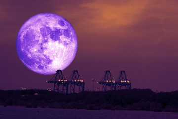 full cold blood moon back on crane of seaport in the night sky