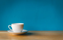 White Cup Of Coffee On Wooden Table With Blue Background
