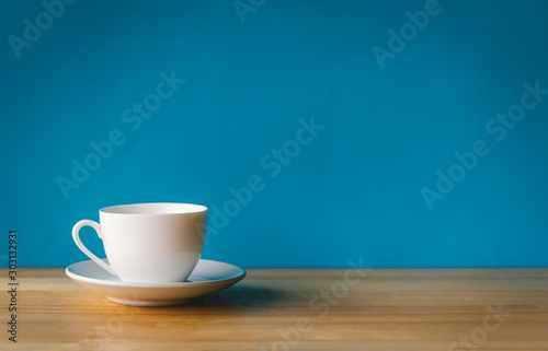 Fotografiet white cup of coffee on wooden table with blue background