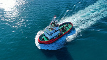 Aerial Drone Photo Of Tug Boat Cruising In High Speed Near Cruise Liner Docked In Mediterranean Port