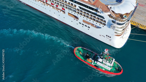 Aerial drone photo of tug boat cruising in high speed near cruise liner docked i Slika na platnu