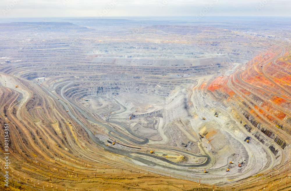 Fototapety, obrazy: Aerial view of opencast mining quarry with lots of machinery at work - view from above.