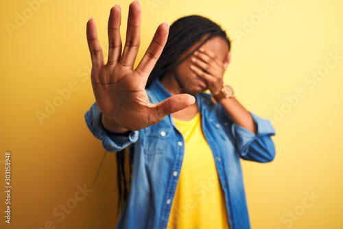 Young african american woman wearing denim shirt standing over isolated yellow background covering eyes with hands and doing stop gesture with sad and fear expression Fotobehang