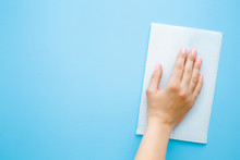 Woman Hand Wiping Pastel Blue Desk With White Paper Napkin. General Or Regular Cleanup. Closeup. Empty Place For Text Or Logo. Top Down View.