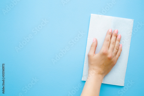 Valokuvatapetti Woman hand wiping pastel blue desk with white paper napkin