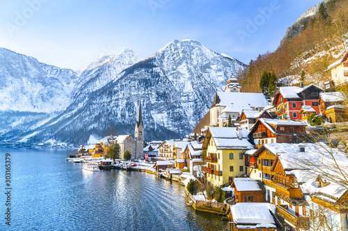 Classic postcard view of famous Hallstatt lakeside town in the Alps with traditional passenger ship on a beautiful cold sunny day with blue sky and clouds in winter, Salzkammergut region, Austria #303165379
