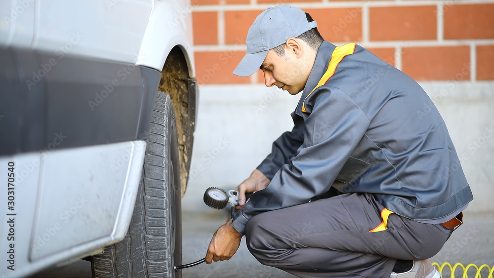 Fototapety, obrazy: Smiling mechanic inflating a van's tire