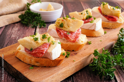 Cuadros en Lienzo Crostini appetizers with brie cheese, salami and artichokes
