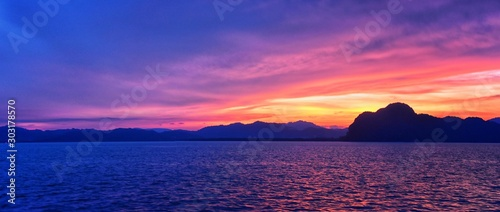 Foto auf AluDibond Dunkelblau Islands Sunset, Ocean panorama views near Phuket with deep Red, Orange, Purple and Blue, mountains, twilight in Thailand. Including Phi Phi, Ko Rang Yai, Ko Li Pe and other islands. Asia.