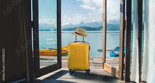 Fotomural  Travel suitcase with hat at house on the lake, summer beach vacation concept