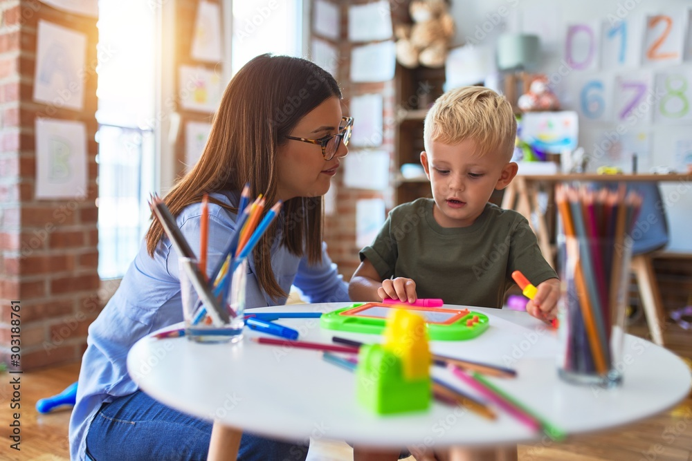 Fototapety, obrazy: Young caucasian child playing at playschool with teacher. Mother and son at playroom drawing a draw with color pencils