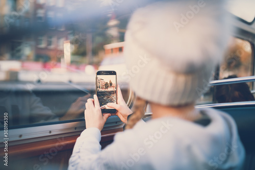 Obraz Young girl taking photo of cityscape with smartphone - fototapety do salonu