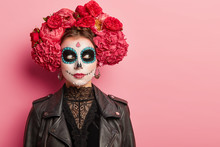 Scary Woman With Skull Makeup, Prepares For Day Of Dead In Mexico, Has Dark Circles Around Eyes, Painted Lips, Wears Peony Wreath And Black Clothing, Ready For Popular Carnival, Isolated On Pink Wall