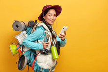 Pretty Satisfied Traveler Uses Free Internet Connection On Smartphone For Blogging During Wanderlust Trip, Carries Big Heavy Rucksack, Has Binoculars And Retro Camera To Explore Surroundings