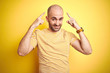 Leinwanddruck Bild - Young bald man with beard wearing casual striped t-shirt over yellow isolated background smiling pointing to head with both hands finger, great idea or thought, good memory