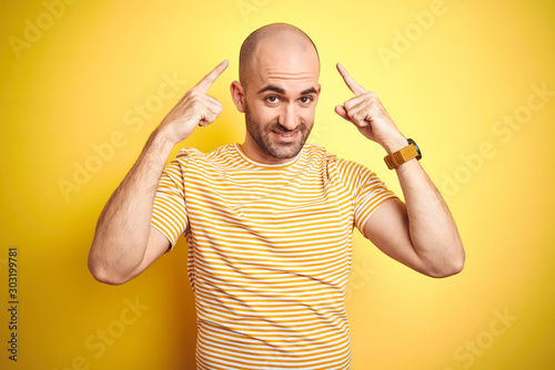 Carta da parati Young bald man with beard wearing casual striped t-shirt over yellow isolated ba