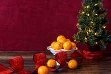 Christmas Treat, Satsuma Oranges In White Bowl, With Artificial Christmas Tree And White Lights, Red Ribbon, Wood Table, Red Background