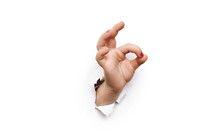 Hand Ok Sign. The Hild's Hand Came Out Into The Hole And Shows Symbol Of Fine. Copy Space.