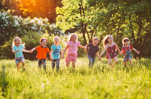 Foto  Large group of kids, friends boys and girls running in the park on sunny summer day in casual clothes