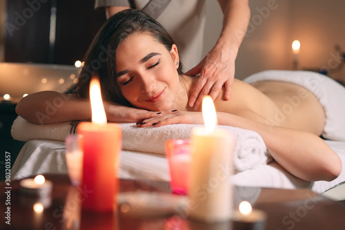 Fototapeta  Spa, massage. Young dark-haired beautiful girl doing massage.