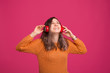 Leinwanddruck Bild - Photo of cheerful young woman, enjoying listening music at headphones, standing over pink background