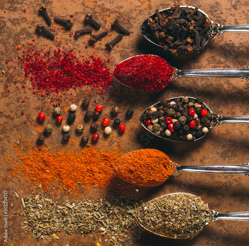 Fotografía The Different Spices. Spices on stone background.