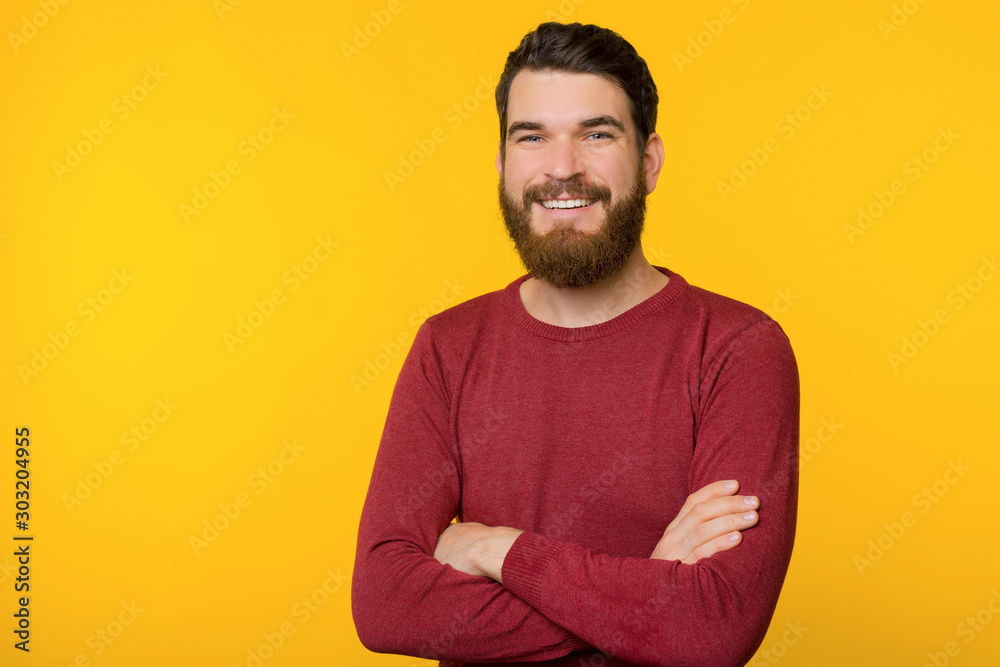 Fototapeta Photo of bearded guy, standing with crossed arms, looking and smiling at camera  over yellow isolated background