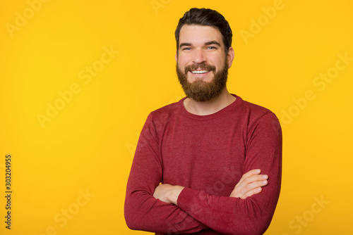 Obraz Photo of bearded guy, standing with crossed arms, looking and smiling at camera  over yellow isolated background - fototapety do salonu