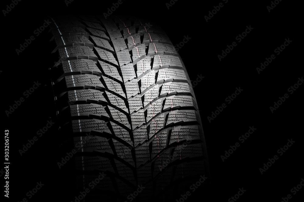 Fototapeta Winter high performance studless tire on black background