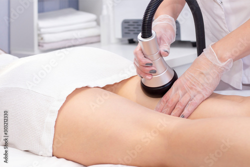 Fotomural  Cosmetologist reducing cellulite on hips of  female patient, using ultrasound cavitation machine