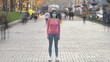 The girl with face mask stands in the crowded street. time lapse