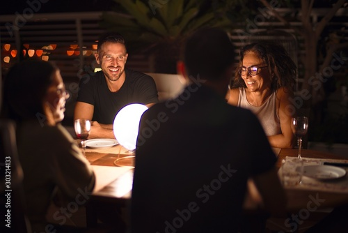 Obraz na plátně  Beautiful family on dinner talking and smiling at terrace