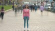 The girl stands on the pavement against the human flow. time lapse