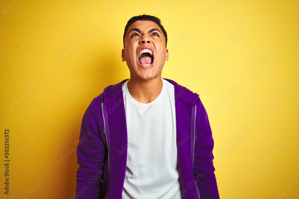 Fototapeta Young brazilian man wearing purple sweatshirt standing over isolated yellow background angry and mad screaming frustrated and furious, shouting with anger. Rage and aggressive concept.