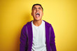 Young brazilian man wearing purple sweatshirt standing over isolated yellow background angry and mad screaming frustrated and furious, shouting with anger. Rage and aggressive concept.