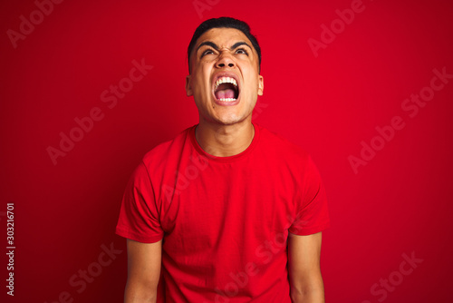 Carta da parati Young brazilian man wearing t-shirt standing over isolated red background angry and mad screaming frustrated and furious, shouting with anger