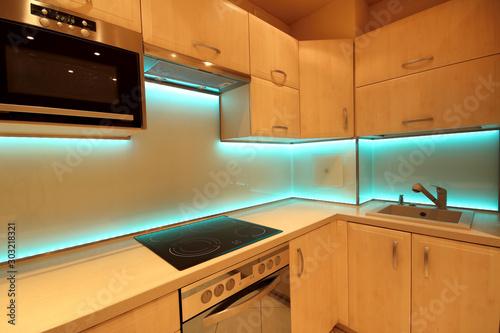 Photo Modern luxury kitchen with custom made furnishings and LED RGB backlit glass