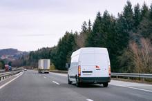 White Minivan In Road. Mini Van Auto Vehicle On Driveway. European Van Transport Logistics Transportation. Auto With Driver On Highway.