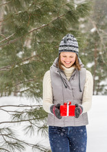 Beautiful, Happy, Smiling Young Woman Holding Christmas Gift Present Outdoors In Snowy Forest. She Is Wearing Warm Clothing A Knit Sweater, Hat And Mittens, Denim Jeans And An Insulated Vest.