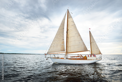 Vintage wooden two mast yacht (yawl) sailing in a open sea on a clear day. Waves and white clouds