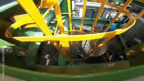 Fotografía  Operation engineer is climbing a vertical ladder inside a petroleum plant