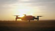 Drone copter flying during sunset. Modern technology and UAV concept.