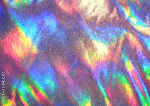 Metallic rainbow holographic texture. Close up of shimmering textile of padded puffer jacket, coat. Fashion trend.