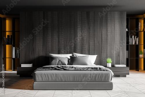 Fototapeta Dark wooden bedroom interior with bookcase obraz
