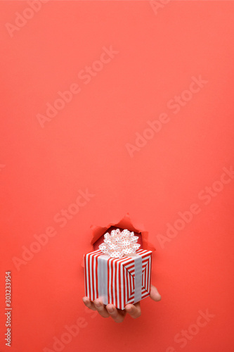 Hand give red and white striped gift box on torn red paper wall Wallpaper Mural