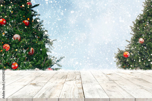 Fotobehang Bomen Top of empty wood table with beautiful Christmas tree and snowfall backdrop. ready for your product display or montage. Concept of background in Christmas and New year holidays.