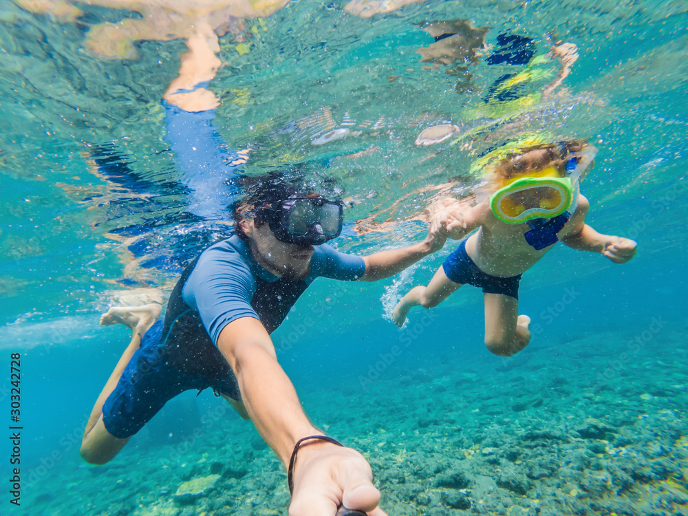 Fototapeta Underwater portrait of father and son snorkeling together